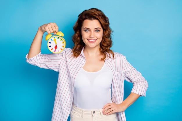 Портрет привлекательной девушки, держащей в руке будильник, забавные часы, изолированные на синем цветном фоне