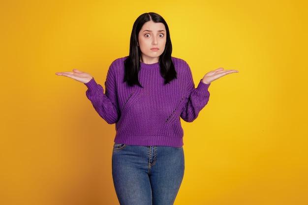 魅力的な女の子の無知な肩をすくめるの肖像画は、黄色の背景に分離されていることを知りません