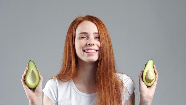 Портрет улыбающейся привлекательной девушки показывает нарезанный авокадо