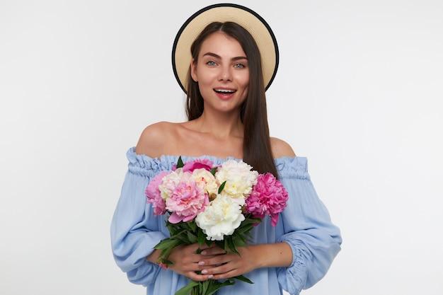 大きな笑顔と長いブルネットの髪を持つ魅力的な女の子の肖像画。帽子と青いかわいいドレスを着ています。美しい花の花束を持っています。白い壁の上に孤立して見ています