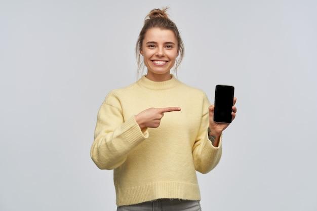 금발 머리를 가진 매력적인 여자의 초상화는 롤빵에 모였다. 노란색 스웨터를 입고 전화 화면을 가리키고 공간을 복사합니다. 넓게 웃고있다. 흰 벽에 고립 된 카메라를 보면
