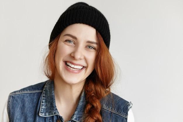 うれしそうな魅力的な笑顔でカメラを見て三つ編みで魅力的な女の子の肖像画