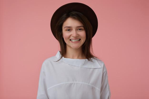 긴 갈색 머리를 가진 매력적이 고 행복 한 여자의 초상화. 흰 블라우스와 검은 모자를 쓰고. 넓은 미소를 지었다. 감정적 인 개념. 파스텔 핑크 벽 위에 절연