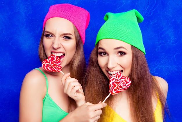 Портрет привлекательных счастливых девушек в шляпах, кусающих леденцы на палочке