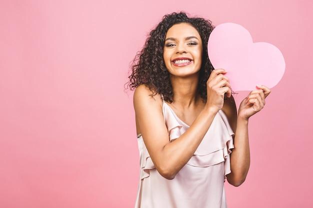 大きなピンクの心を持つピンクの背景に対して分離された魅力的な幸せな笑顔のアメリカのアフロ女性の肖像画