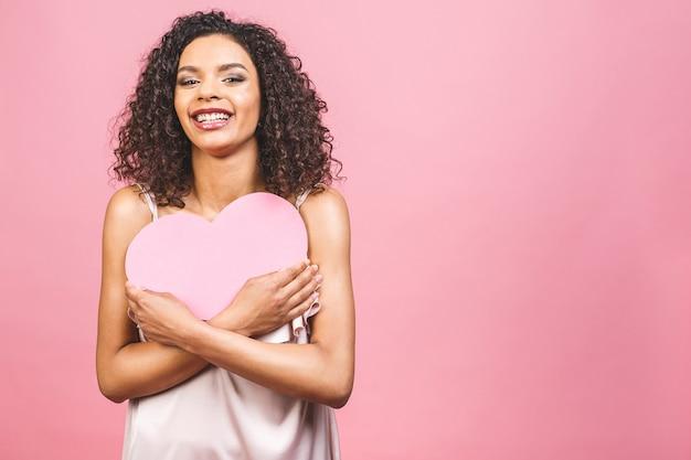 大きなピンクの心を持つピンクの背景に対して分離された魅力的な幸せな笑顔のアメリカのアフロ女性の肖像画。