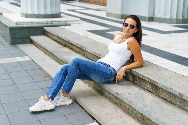 白いtshiのサングラスを身に着けている街の通りの階段に座っている魅力的な幸せな女性の肖像画...