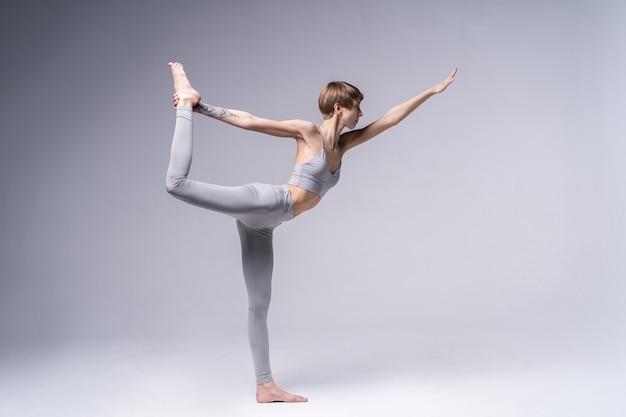Портрет привлекательной счастливой молодой женщины, работающей в помещении, делая упражнения йоги