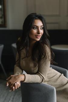 Портрет привлекательной индийской женщины носить модные элегантные платья, сидя на диване и ждет такси. веселая азиатская фотомодель позирует для фоток в студии