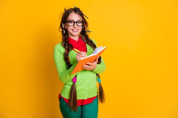 Портрет привлекательной интеллектуальной прилежной веселой девочки-подростка, пишущей эссе, делая домашнее задание, изолированное на ярко-желтом цветном фоне