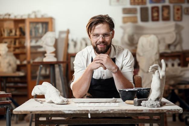 워크숍 인테리어 배경에 앉아 미소로 카메라를 보이는 매력적인 즐거운 수염 된 남성 조각가의 초상화.