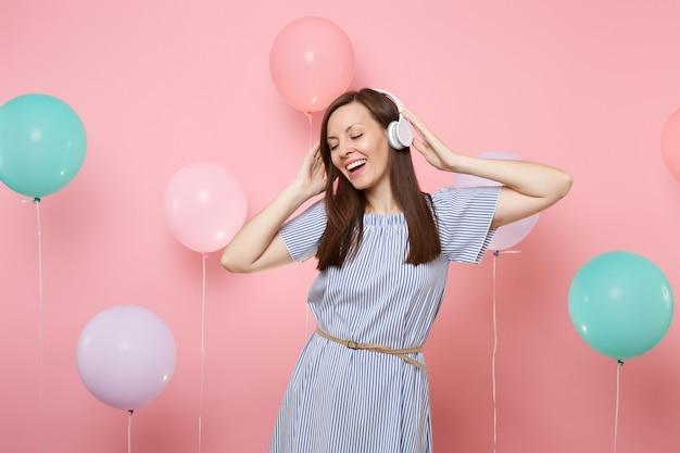 Портрет привлекательной радостной молодой женщины с закрытыми глазами с наушниками в голубом платье, слушая музыку на розовом фоне с красочными воздушными шарами. день рождения праздник у людей искренние эмоции.