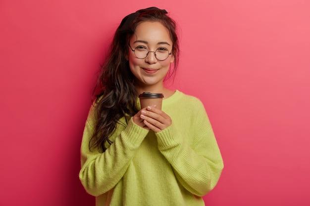 魅力的な韓国の女の子の肖像画は、持ち帰り用のコーヒーと一緒に立って、カフェイン飲料を楽しんで、優しい幸せな表情で見えます