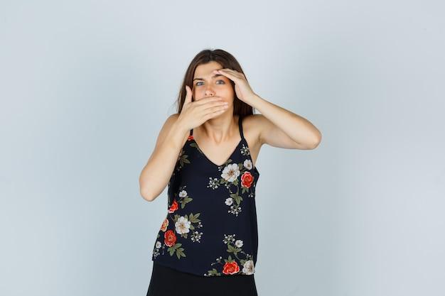 한 손을 머리 위로 잡고 다른 손으로 블라우스를 입고 입을 가리고 문제가 있는 앞모습을 바라보는 매력적인 여성의 초상화