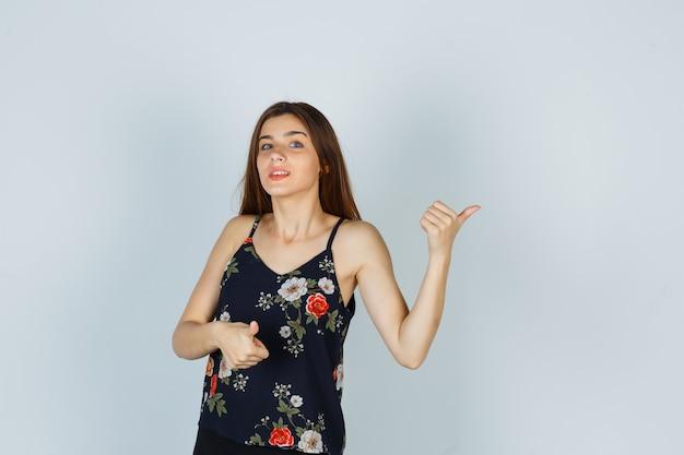 Портрет привлекательной дамы показывает палец вверх в блузке и выглядит уверенно, вид спереди