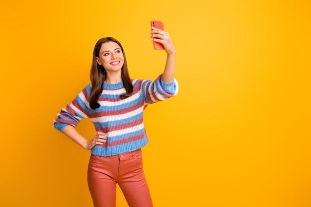 Портрет привлекательной милой девушки, делающей селфи, удерживая телефон