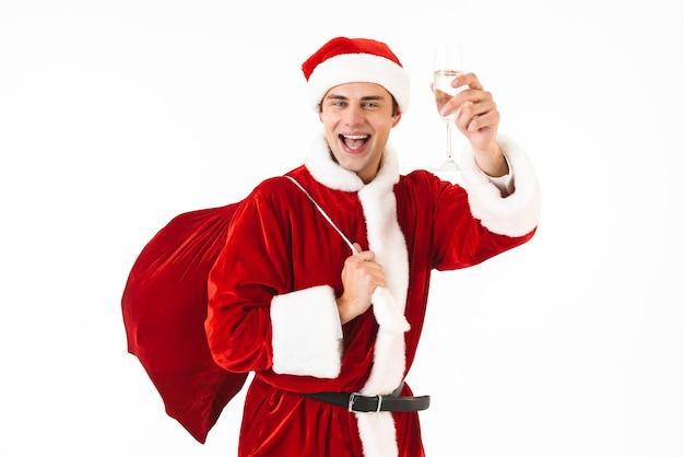 Портрет привлекательного мужчины 30-х годов в костюме санта-клауса и красной шляпе, держащего подарочный пакет и бокал с шампанским Premium Фотографии
