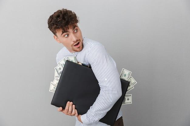 회색 벽에 격리된 현금 뭉치를 들고 외교관을 안고 궁금해하는 셔츠를 입은 매력적인 남자의 초상화