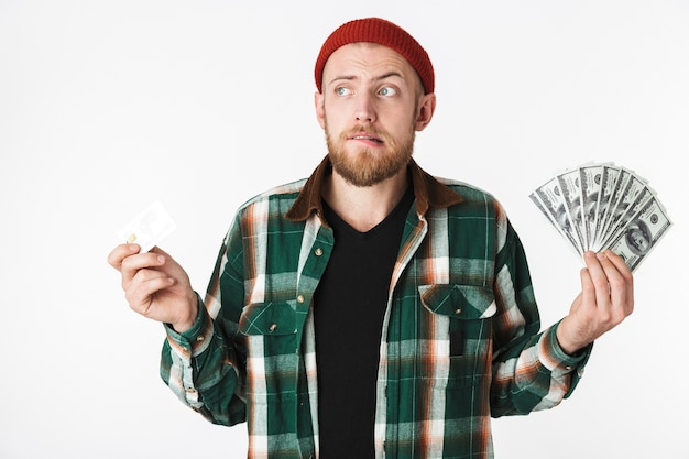 Портрет привлекательного мужчины, держащего кредитную карту и поклонника долларовых денег, стоя изолированным на белом фоне