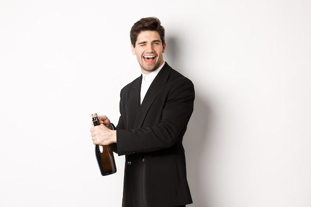黒いスーツを着た魅力的な男性の肖像画、カメラでウィンクし、シャンパンのボトルを開けて、新年を祝って、白い背景に立っています。