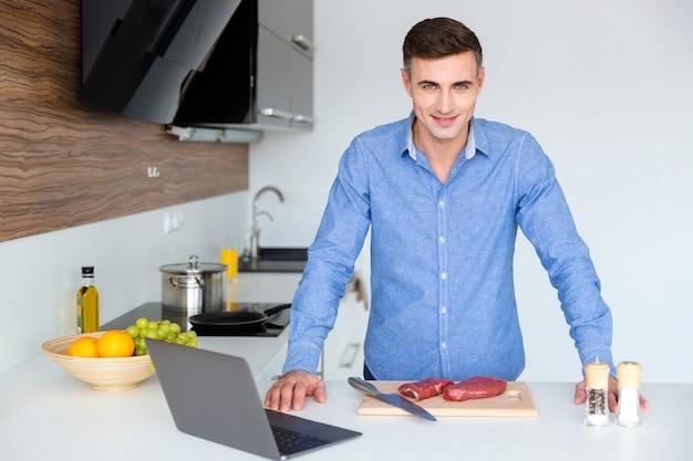 Портрет привлекательного мужчины в синем дерьме с ноутбуком, готовящего мясо на кухне