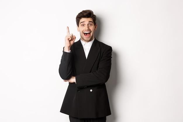 スーツを着た魅力的な男性の肖像画、アイデアを持って、興奮して立って、提案、思考の解決策、白い背景の上に立っていることを伝えるために1本の指を上げる