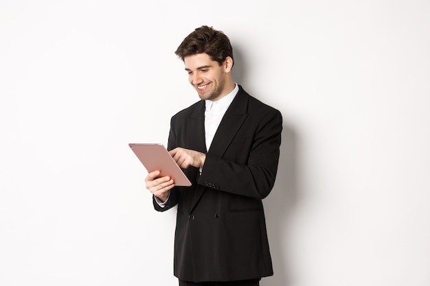 최신 유행의 정장을 입은 매력적인 남자의 초상화, 디지털 태블릿을 보고 웃고, 온라인 쇼핑, 흰색 배경 위에 서 있는