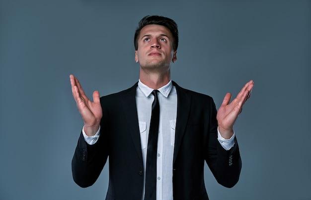灰色で隔離、手を上げて祈る魅力的なマネージャーの肖像画。希望と信念の概念。