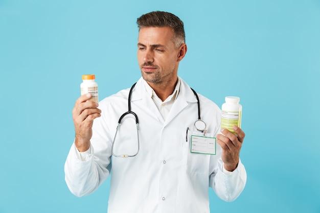青い壁の上に孤立して立って、錠剤の瓶を保持している白いコートを着ている魅力的な医療専門家の肖像画
