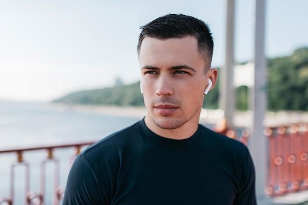 Портрет привлекательного мускулистого спортсмена, слушающего музыку, нося наушники