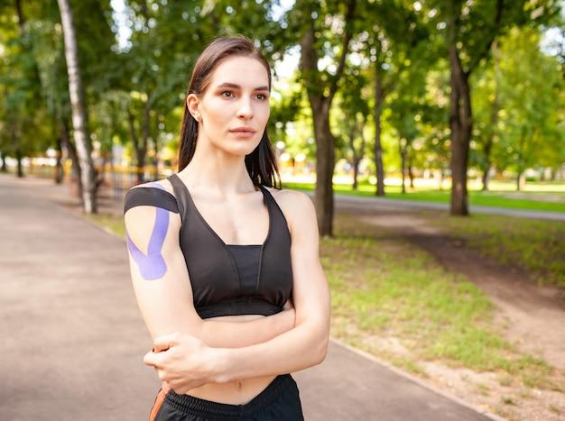 블랙 스포츠 옷을 입고 매력적인 근육 갈색 머리 여자의 초상화