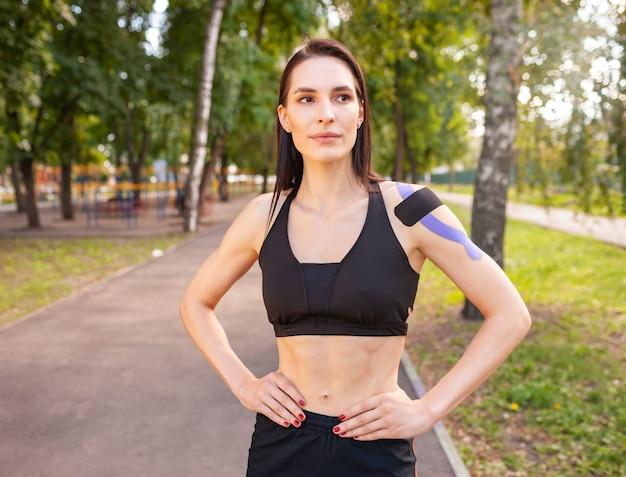 黒のスポーツ服を着ている魅力的な筋肉のブルネットの女性の肖像画