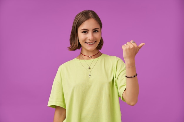 매력적이 고 좋은 찾고 여자의 초상화입니다. 웃 고 보라색 벽 위에 복사 공간에서 오른쪽 엄지 손가락을 가리키는. 녹색 티셔츠, 치아 교정기, 목걸이 및 팔찌 착용