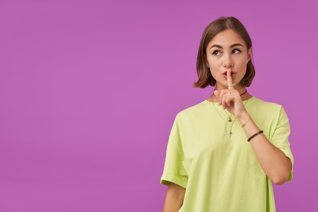 매력적이 고 좋은 찾고 여자의 초상화입니다. 손가락으로 입술을 만지고 침묵 기호를 표시합니다. 보라색 벽을 통해 복사 공간에서 왼쪽을보고 있습니다. 녹색 티셔츠, 팔찌 및 반지 착용