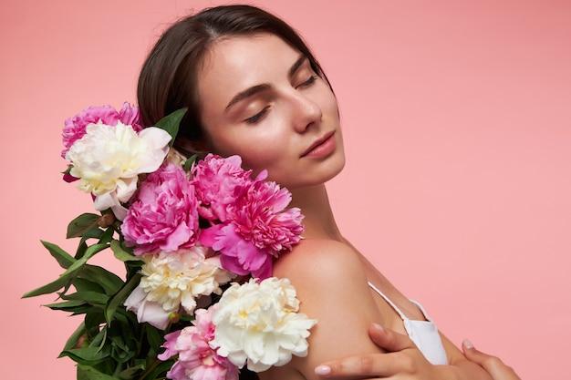 긴 갈색 머리, 닫힌 눈과 건강한 피부를 가진 매력적이고 좋은 찾고 여자의 초상화. 흰 드레스를 입고 꽃의 꽃다발을 들고 있습니다. 파스텔 핑크 벽 위에 절연 스탠드