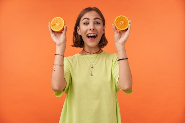 オレンジと笑顔を示す短いブルネットの髪を持つ魅力的で見栄えの良い女の子の肖像画。ジュースを作る準備をしています。緑のtシャツ、歯列矯正器、ブレスレットを着用