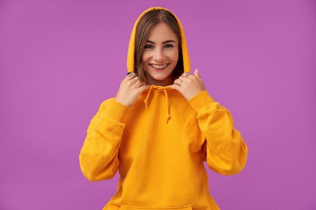 짧은 갈색 머리를 가진 매력적이 고 좋은 찾고 여자의 초상화. 미소하고 보라색 벽 위에 손으로 후드를 만지고. 주황색 후드 티, 반지 및 치아 교정기 착용
