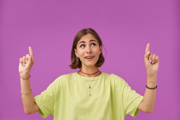 魅力的で見栄えの良い、不思議な女の子の肖像画。紫色の壁の上のコピースペースに指を向けます。緑のtシャツ、歯列矯正器、ネックレス、ブレスレット、指輪を身に着けている