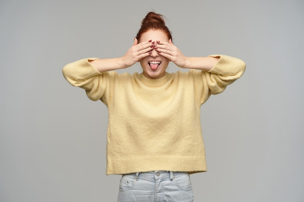 머리를 가진 매력적이 고 쾌활 한 빨간 머리 여자의 초상화는 롤빵에 모여. 파스텔 옐로우 스웨터와 청바지를 입고. 손바닥으로 눈을 가리고 혀를 보여줍니다. 회색 벽 위에 절연 스탠드