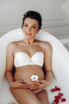 おへそに白い花と水中の赤いバラとお風呂に横たわっている白いブラジャーの魅力的な妊娠中の大人のブルネットの肖像画。笑顔の妊婦