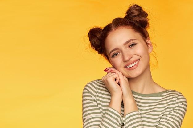 2つのパンを持つ魅力的な赤い髪の少女の肖像画。ストライプのセーターを着て、手をつなぎます。左側のスペースをコピーします。優しく見て、クローズアップ、黄色の壁に隔離