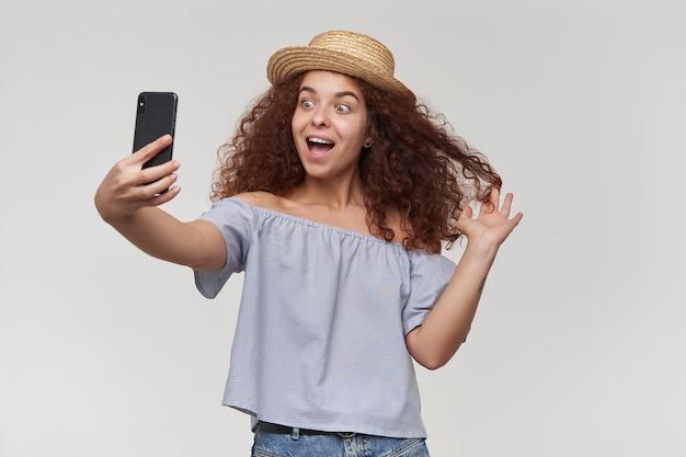 곱슬 머리를 가진 매력, 빨간 머리 여자의 초상화. 스트라이프 오프 숄더 블라우스와 모자 착용. 스마트 폰으로 셀카를 찍고, 머리와 미소를 지으며 놀아보세요. 흰 벽 위에 절연 스탠드