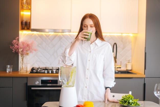 건강한 야채 해독 스무디 주스를 마시는 매력적인 빨간 머리 젊은 여성의 초상화