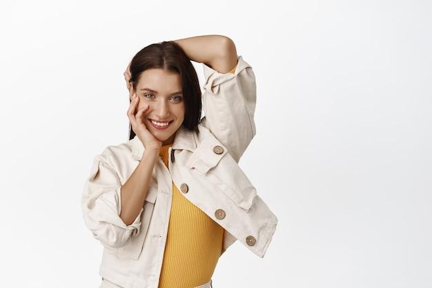 魅力的な生意気な女性の肖像画、コケティッシュな大胆な笑顔、彼女の頭、髪、顔に触れ、スタイリッシュな衣装で軽薄なポーズをとり、白の上に立っています。コピースペース
