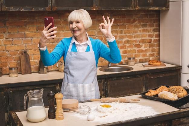 Портрет привлекательной старшей постаретой женщины варит на кухне. бабушка делает вкусную выпечку.