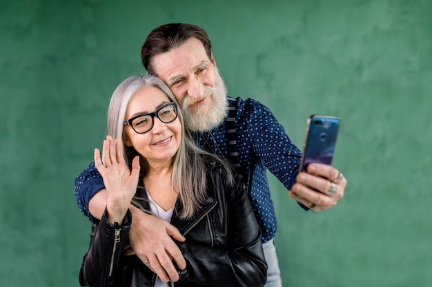 緑の壁の前に家に立って、魅力的な年配のカップルの肖像画