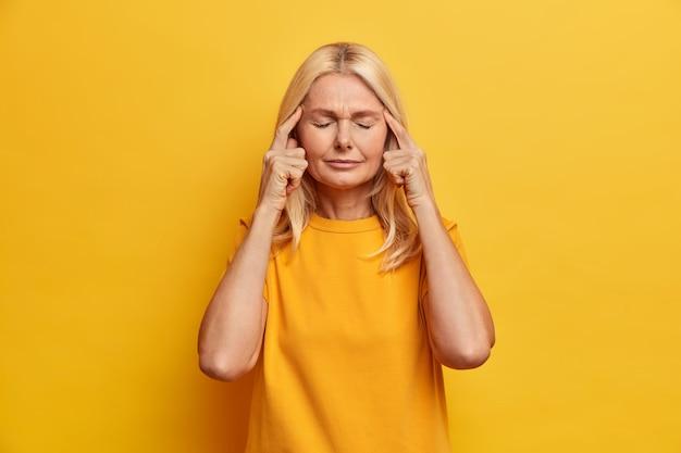 Портрет привлекательной пожилой женщины стоит с закрытыми глазами, держит пальцы на висках, думает о чем-то и пытается найти решение, имеет плохую память, одет в повседневную одежду