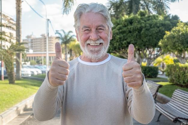 Портрет привлекательного старшего мужчины, стоящего на открытом воздухе в общественном парке с большими пальцами руки вверх. белые волосы улыбающиеся люди смотрят в камеру, выражая радость и позитив