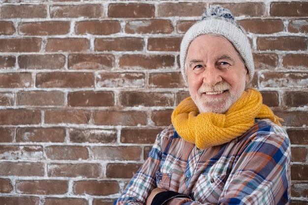 Портрет привлекательного старшего человека в зимнем платье, стоящего против кирпичной стены, глядя на камеру улыбается. кирпичная стена в фоновом режиме