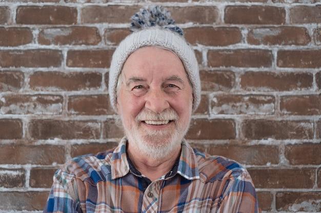 Портрет привлекательного старшего мужчины в зимнем платье, стоящего у кирпичной стены, глядя в камеру, улыбаясь